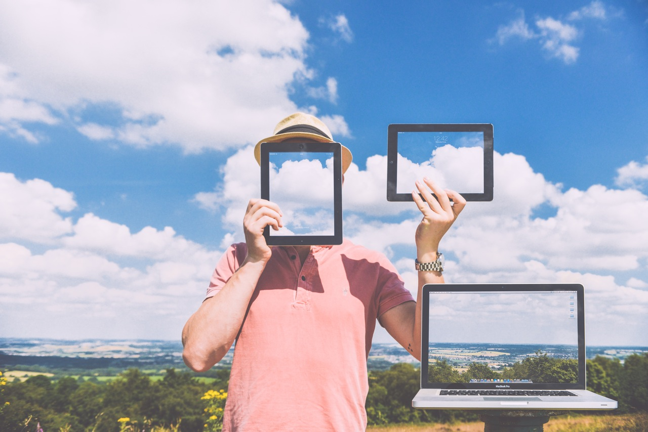 Man holding up tablet screens in front of cloudy sky