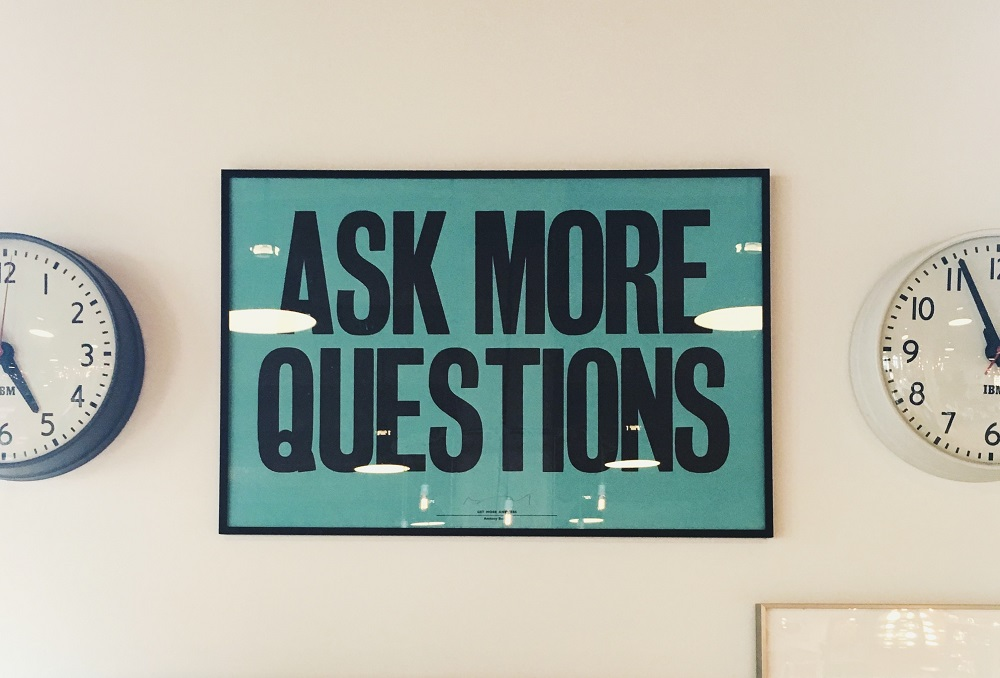 Framed sign hanging on an office wall which says ask more questions