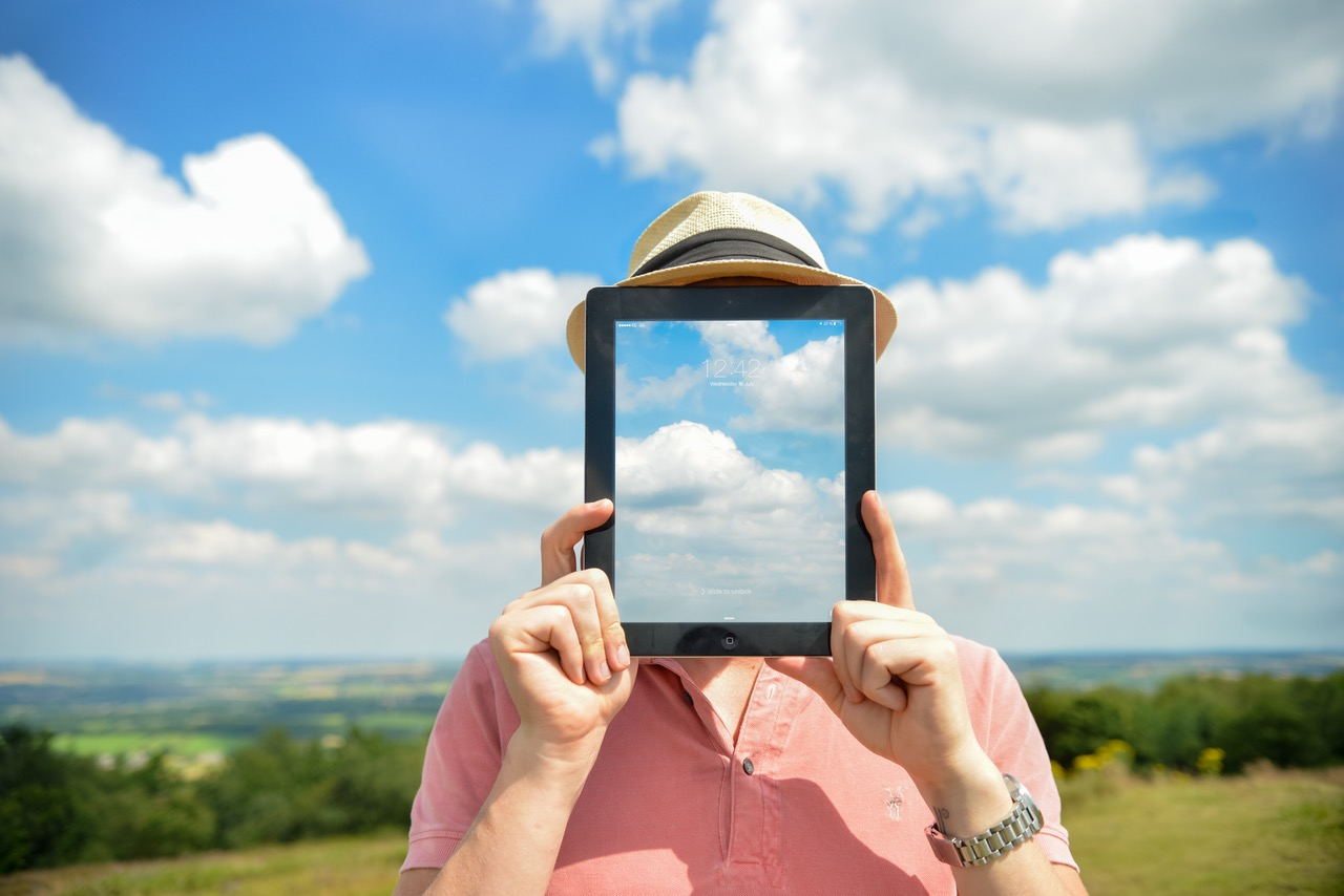 Man holding an Ipad with background of clouds